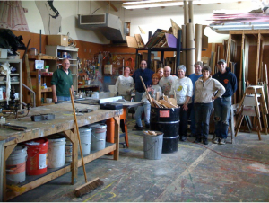 """PAC RATs cleaning up a """"pack rat nest"""" and recycling paint in the scene shop at the Newport Performing Arts Center.  Left to right: Mark McConnell, Linda Annable, Sean Brateng, Vickie Steen, Sandee Staufenbeil, Stephan, Khloella Brateng, Tim, Kate Sanella, Rick LeDoux."""
