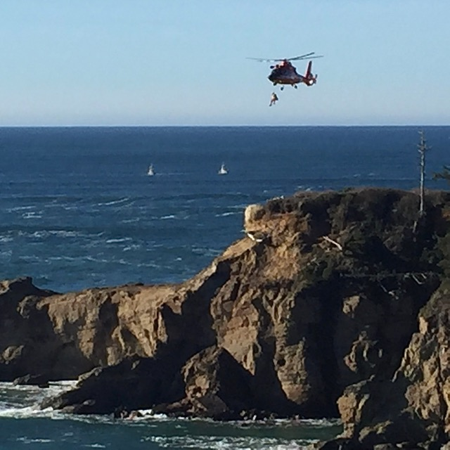 Coast Guard Helo lifts stranded kayaker up off the rocks below, heads to cliff top.