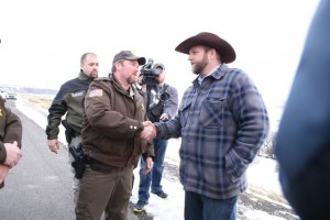 Harney County Sheriff Dave Ward and Malheur NWR HQ vigilante leader Ammon Bundy shake hands and talk outside the refuge.