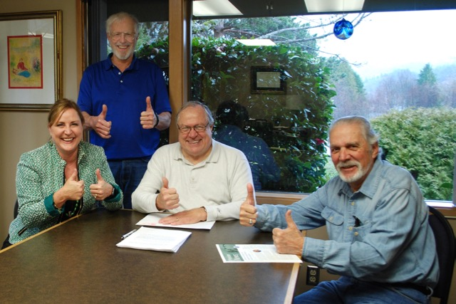 Signing the final documentation Dr. Lesley Ogden (L), representing Samaritan North Lincoln Hospital, and NLHD board members David Hess (standing), Terry Buggenhagen (C) and Mike Holden (R)