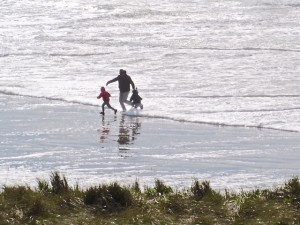 Father and kids run, with their backs to the water - totally vulnerable to a sneaker wave.