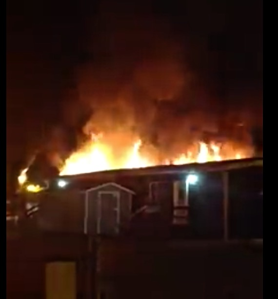 """""""The Play Shed"""" burning behind the blue building."""