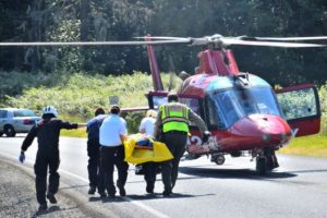 Victim is carried to an awaiting REACH medical chopper to take her to trauma center in Corvallis.