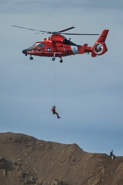 Coast Guard chopper and crewman saving two stranded young men above Roads End.