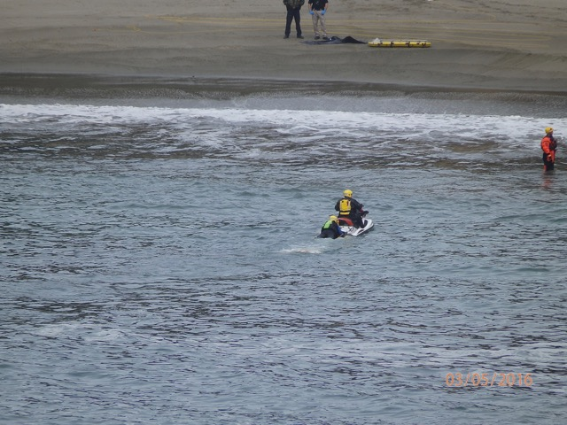 Body being delivered to the beach at Whale Cove