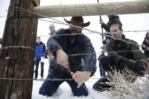 Occupier Ammon Bundy cutting a fence so a rancher's cows could graze on Malheur Wildlife Refuge land. Oregonian photo