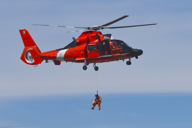 Coast Guard arrives on scene - lowers rescue crewman.