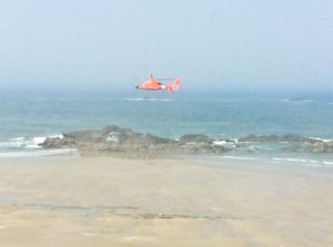 Coast Guard helo searches near and far shore for report of missing man clinging to a fishing boat tote.  Tote came ashore without him attached.
